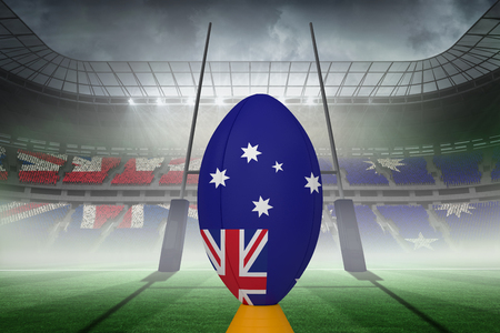 red ball: Australian flag rugby ball on stand against rugby pitch Stock Photo