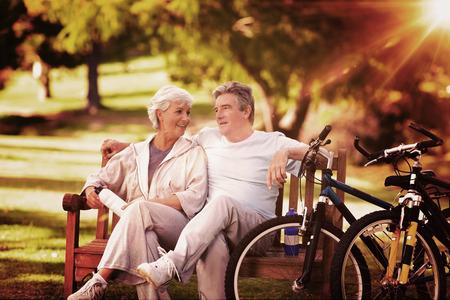 jubilados: Pareja de ancianos con sus bicicletas contra haz de luz