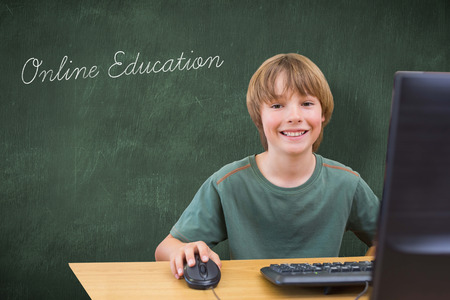 internet education: The word online education and school kid on computer against green chalkboard Stock Photo