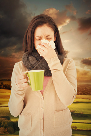 holding nose: Sick woman blowing her nose while holding a green mug against country scene
