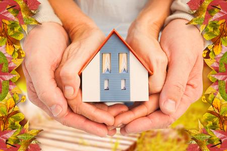Couple holding kleines Modell Haus in den Händen gegen Herbst-Szene