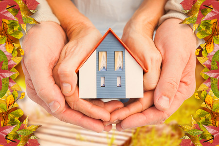 Couple holding small model house in hands against autumn scene Stock Photo