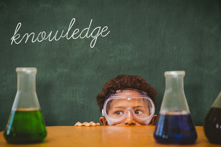 make believe: The word knowledge and cute pupil dressed up as scientist against green chalkboard Stock Photo