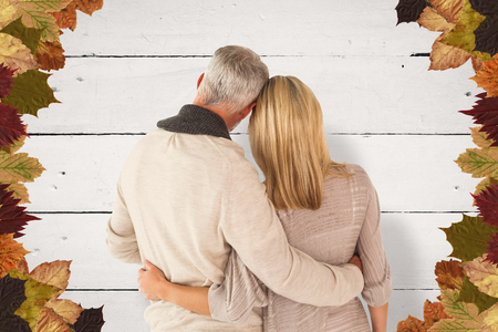 arms around: Rear view of couple with arms around against white wood Stock Photo