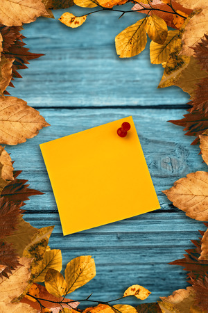 digital image: Digital image of pushpin on yellow paper  against autumn leaves pattern