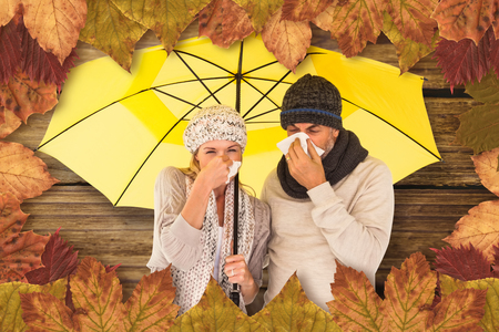 realtionship: Couple sneezing in tissue while standing under umbrella against wooden background
