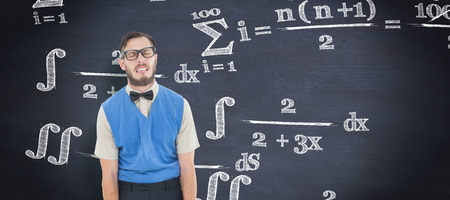 silly face: Geeky hipster pulling a silly face against blackboard Stock Photo