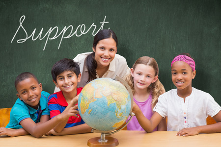 The word support and cute pupils and teacher looking at globe in library against green chalkboard Stock Photo