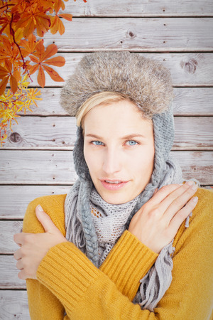 shivering: Woman in winter clothes shivering over white background against autumn leaves pattern