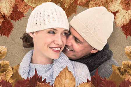 warm clothing: Casual couple in warm clothing against autumn leaves pattern Stock Photo
