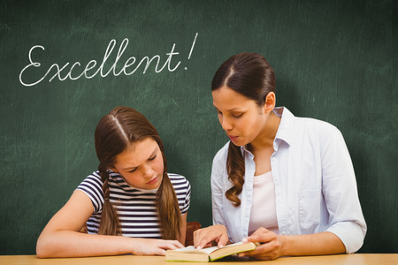excellent: The word excellent! and teacher and girl reading book in library against green chalkboard Stock Photo