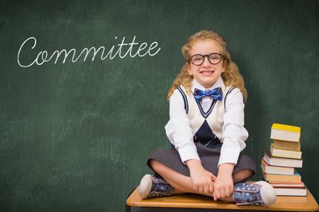 comité d entreprise: Le comité de mot et de l'élève mignon assis sur la table contre le tableau vert Banque d'images