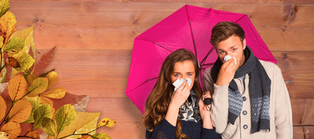 blowing nose: Couple blowing nose while holding umbrella against bleached wooden planks background