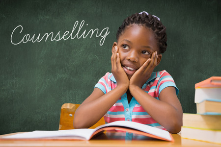 counselling: The word counselling and pupil sitting at her desk  against green chalkboard Stock Photo