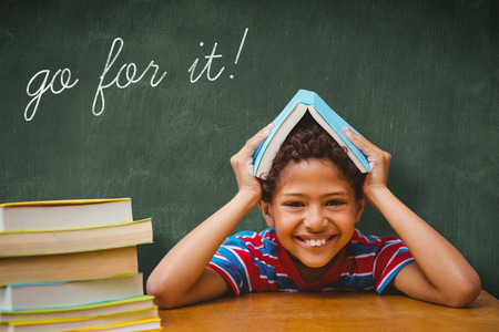 go for: The word go for it! and pupil with many books against green chalkboard Stock Photo