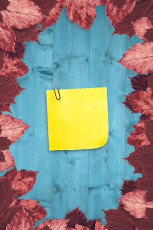 inscribe: Sticky note with grey paperclip against autumn leaves on wood
