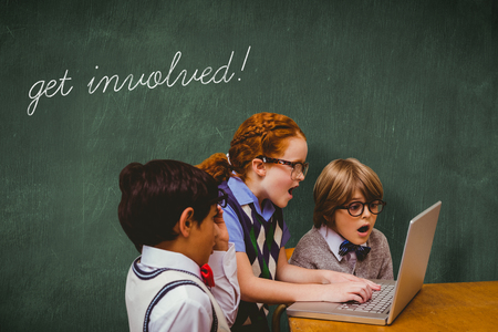 involved: The word get involved! and pupils using laptop against green chalkboard Stock Photo