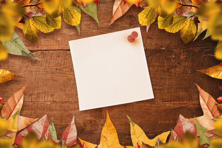 yellow pushpin: Digital image of pushpin on yellow paper  against autumn leaves on wood