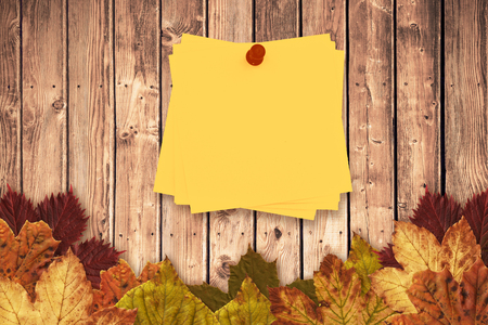 red pushpin: Sticky note with red pushpin against autumn leaves on wood