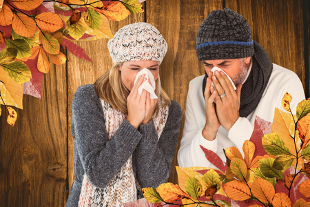 sneezing: Couple sneezing in tissue against wooden table Stock Photo
