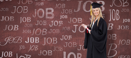 Robe: Blonde student in graduate robe holding a diploma against desk Stock Photo