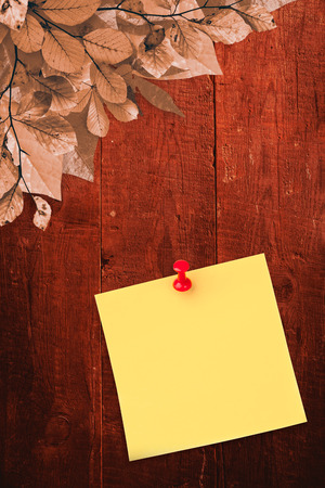 yellow pushpin: Illustrative image of pushpin on yellow paper  against autumn leaves on wood