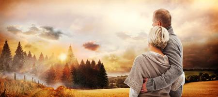 mujer mirando el horizonte: Feliz pareja madura en ropa de invierno contra la escena del pa�s