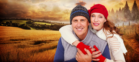 warm clothing: Happy couple in warm clothing against country scene Stock Photo