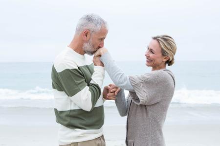 hombre romantico: Romantic man kissing womans hand at the beach