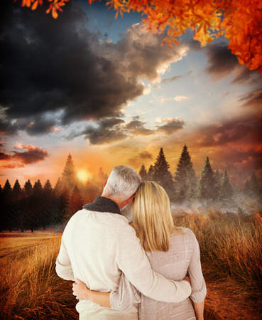 arms around: Rear view of couple with arms around against country scene