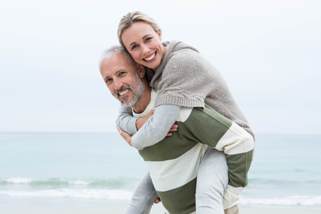 Man giving his partner a piggy back at the beach Stock Photo