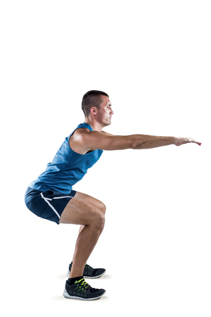 health concern: Full length of fit man doing squats on white background