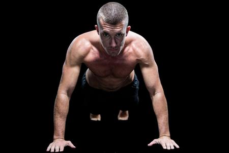 push ups: Portrait of fit shirtless athlete doing push ups against black background