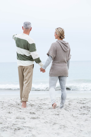warm clothing: Woman holding a mans hand at the beach
