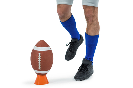 kick ball: Low section of American football player being about to kick ball against white background