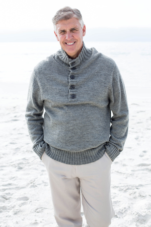 short wave: Smiling man standing in the sand at the beach