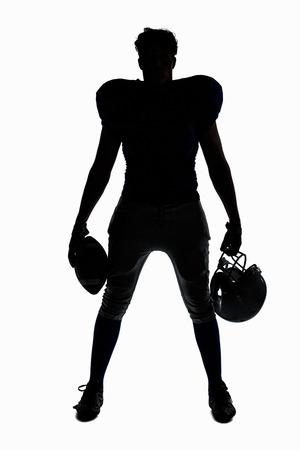 futbolista: Jugador de fútbol americano de la silueta que sostiene la bola y casco contra el fondo blanco