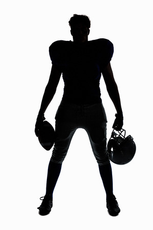 american football: Silhouette American football player holding ball and helmet against white background Stock Photo