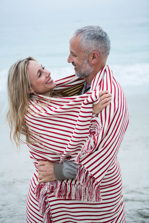short wave: Couple embracing while wrapped in a beach towel by the sea Stock Photo