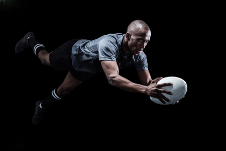 rugby ball: Sportsman jumping for catching rugby ball over black background