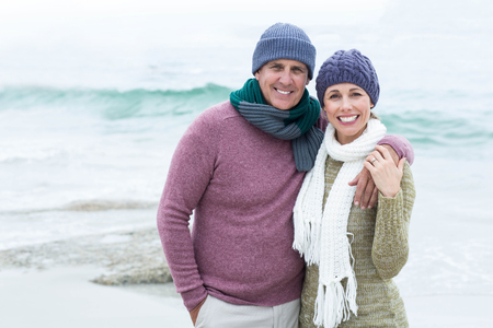 50s women: Smiling happy couple hugging each other at the beach Stock Photo