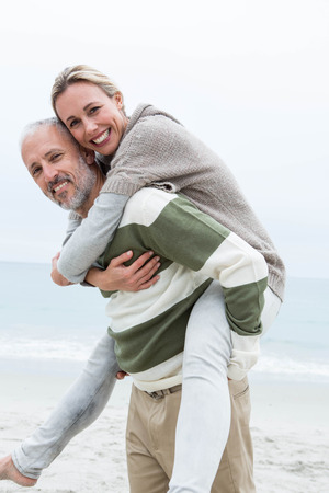 short wave: Man giving his partner a piggy back at the beach Stock Photo