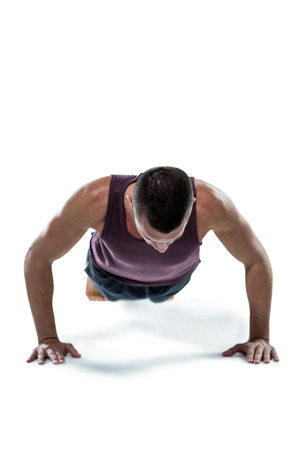 push ups: Fit man in sportswear doing push ups against white background Stock Photo