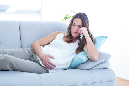 Sad pregnant woman lying on sofa at home