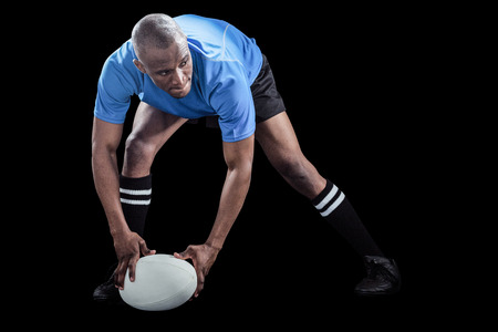 agility people: Sportsman bending and holding ball while playing rugby on black background