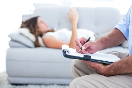 therapy: Therapist writing on notepad with female patient in background