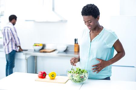 pepe nero: Donna che ha insalata in piedi in cucina a casa Archivio Fotografico
