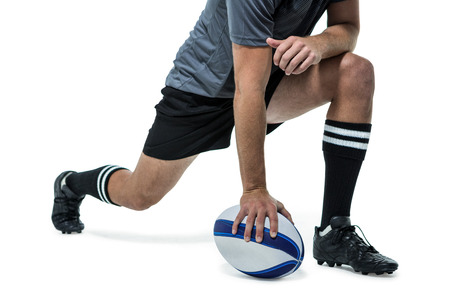 ball stretching: Low section of rugby player in black jersey stretching with ball against white background