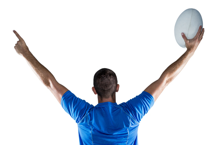 rugby ball: Rear view of rugby player holding ball with arms raised against white background