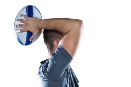 cut the competition: Profile view of rugby player throwing ball against white background